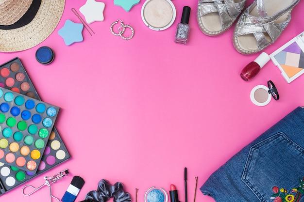 Prodotti cosmetici; paio di scarpe; vestiti e cappello su sfondo rosa