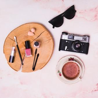 Prodotti cosmetici su ceppo d'albero; tazza di caffè; macchina fotografica d'epoca e occhiali da sole su sfondo rosa con texture