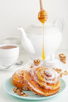 Prodotti da forno fatti in casa. miele di versamento sul panino rotolato dolce con le noci e la noce di cocco grattugiata su bianco