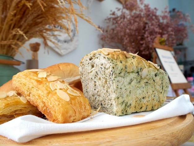 Prodotti da forno freschi in vassoi di legno e chicchi di grano disposti su un tavolo, lino bianco