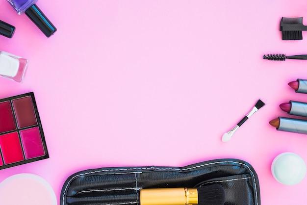 Prodotti di bellezza cosmetici disposti su sfondo rosa con spazio vuoto per il testo