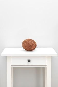 Prodotti di cocco fatti in casa sul fondo della tavola in legno bianco. cocco intero sul tavolo bianco. concetto tropicale di estate