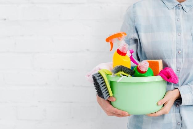 Prodotti di pulizia della tenuta della donna del primo piano