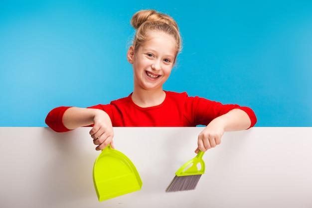 Prodotti di pulizia graziosi di una tenuta della bambina che fanno lavori domestici