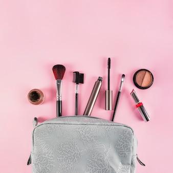 Prodotti di trucco che si rovesciano da una borsa su fondo rosa