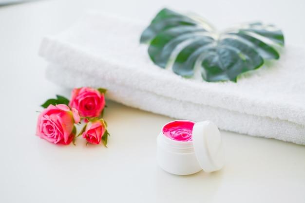 Prodotti e cosmetici per il benessere. cura della pelle a base di erbe e minerali. vasetto di crema, flaconi per la cosmetica bianchi. senza etichetta. spa set con sapone e asciugamano bianco