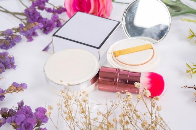 Prodotti e fiori cosmetici su bianco