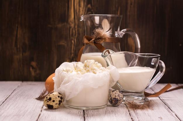 Prodotti lattiero-caseari biologici (latte, panna acida, fiocchi di latte) e uova fresche di gallina e quaglia su legno