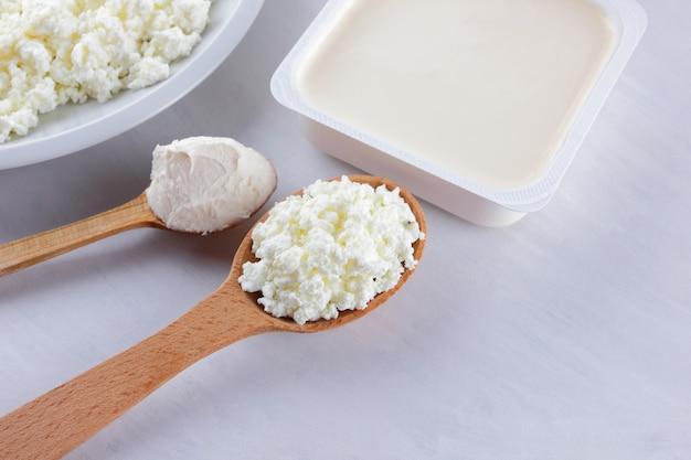Prodotti lattiero-caseari su una lavagna bianca. ricotta, crema e formaggio a pasta molle su una priorità bassa bianca