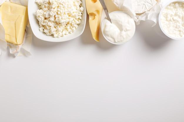 Prodotti lattiero-caseari sulla tavola bianca con copyspace