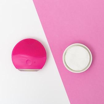 Prodotti per l'igiene e la bellezza delle donne, spazzola elecrtic rossa per il viso e batuffoli di cotone su carta bianca e rosa. trattamento facciale. stile piatto laico. vista dall'alto.