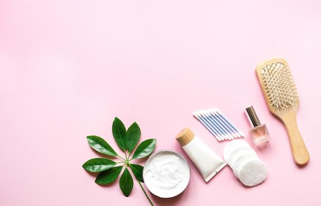 Prodotti per l'igiene quotidiana con un batuffolo di cotone, un asciugamano, una crema e una lozione sul tavolo rosa con vista dall'alto
