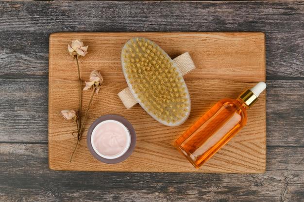 Prodotti per la cura della pelle su uno spazio di legno. spazzole per massaggio anticellulite. . spazzola per massaggi. accessori per il massaggio. flatley. concetto di cura dell'eco. prodotti per la cura della pelle su bianco.