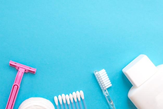 Prodotti per la cura personale. bottiglia bianca, rasoio, padiglioni auricolari, batuffoli di cotone, spazzolino da denti su ba blu