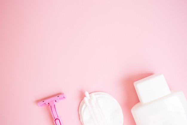 Prodotti per la cura personale. bottiglia bianca, rasoio, tappi per le orecchie, tamponi di cotone su sfondo rosa. c