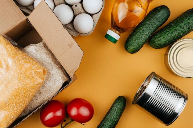 Prodotti per la donazione su uno sfondo giallo. verdure, cereali e conserve. le donazioni di cibo copiano lo spazio.