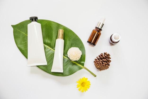 Prodotto cosmetico spa su foglia con olio essenziale; pigna; e fiori su sfondo bianco