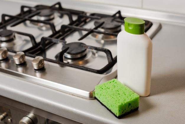 Prodotto detergente per la pulizia e spugna sul fornello a gas