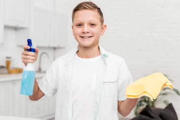 Prodotto di pulizia felice della tenuta del ragazzo