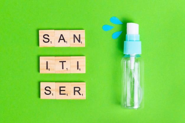 Prodotto disinfettante in spray su uno sfondo verde con gocce blu per proteggere la salute da batteri e virus