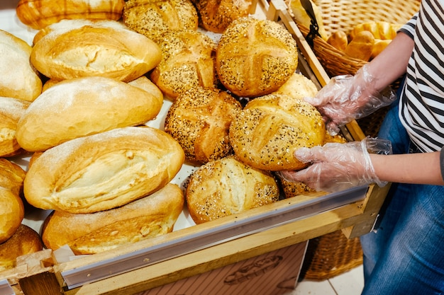 Prodotto in lotti delle pasticcerie del rotolo delle baguette della grana marrone del fondo dell'alimento della mano del femle del pane al forno