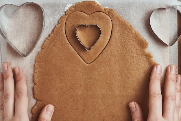Produrre biscotti di panpepato a forma di cuore per san valentino. taglierina del biscotto di uso della mano della donna. concetto di cibo per le vacanze