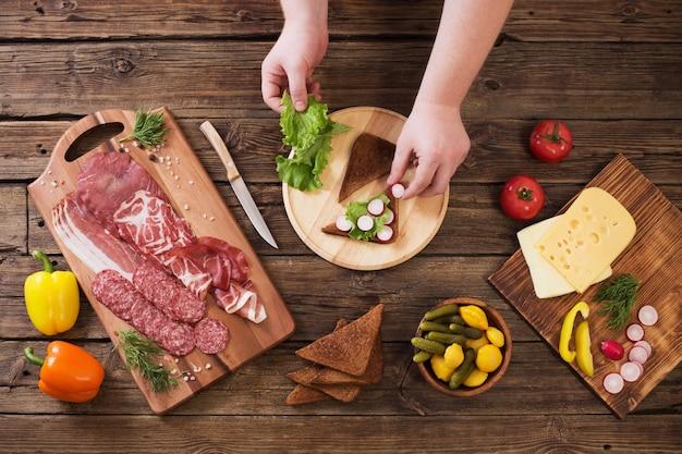 Produrre panini con carne e salsiccia sul tavolo di legno