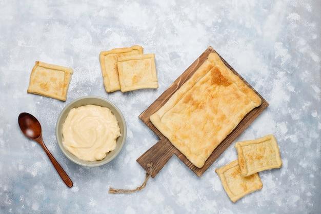 Produrre pasta sfoglia deliziosa fresca con crema pesante su calcestruzzo, vista dall'alto