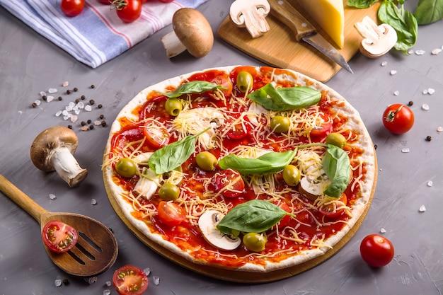 Produrre pizza fatta in casa con pasta con funghi, pomodori e formaggio
