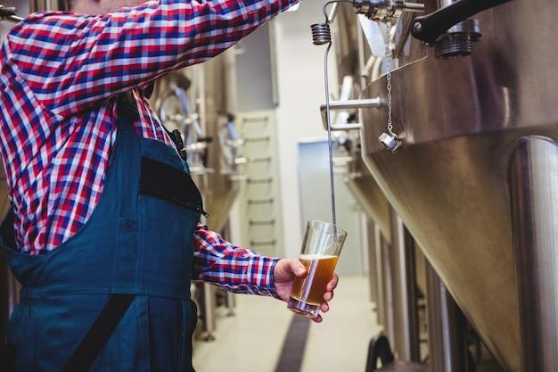 Produttore che riempie birra dal serbatoio