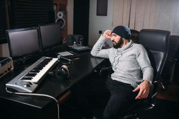 Produttore del suono con microfono in studio musicale