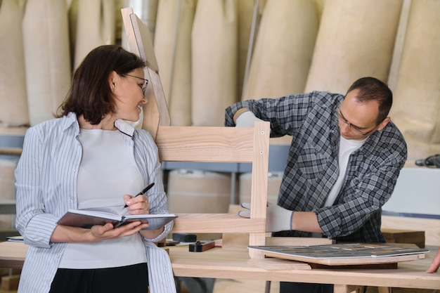 Produzione di falegnameria di mobili, falegname maschio di lavoro e imprenditore femminile con notebook