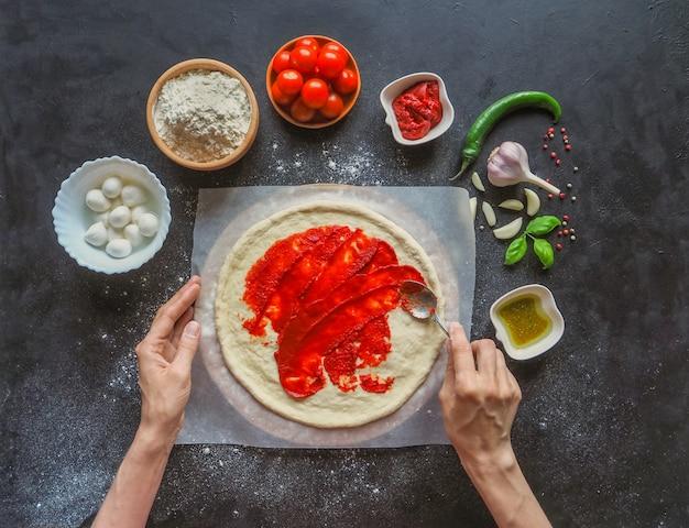 Produzione di pizza italiana margarita. fase di produzione. salsa di pomodoro, mozzarella e pomodori
