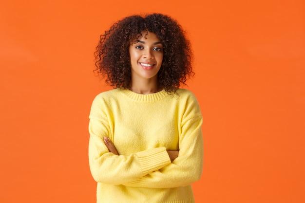 Professionalità, affari e concetto di persone. collaboratrice femminile afroamericana abbastanza sicura e creativa con capelli ricci, mani incrociate sul petto, telecamera assertiva e sicura di sé, sorridente