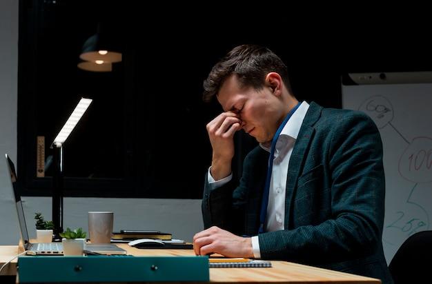 Professionista adulto stanco dopo aver lavorato di notte