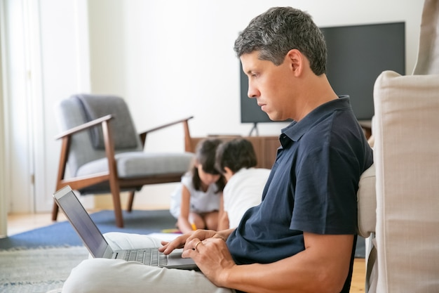 Professionista serio che lavora a casa, seduto sul pavimento e utilizzando il laptop