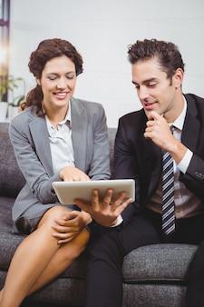 Professionisti sorridenti di affari che per mezzo della compressa digitale