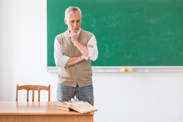 Professore anziano premuroso che sta contro la lavagna verde