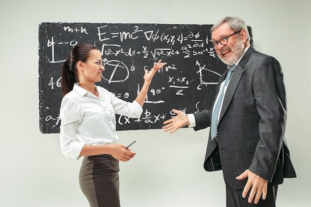 Professore maschio e giovane donna contro la lavagna in aula