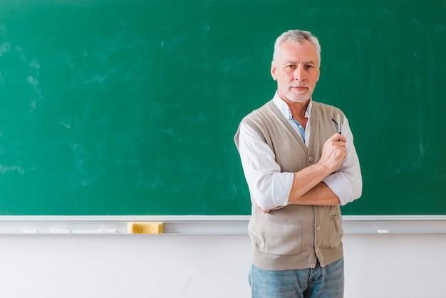 Professore maschio senior che sta contro la lavagna verde