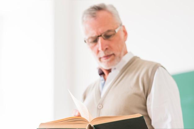 Professore maschio senior in vetri che legge libro