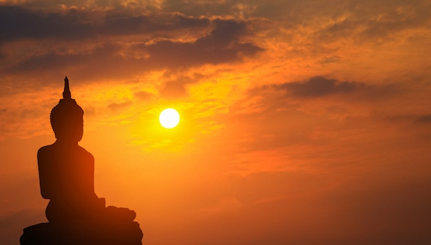 Profili buddha su un fondo del tramonto che splende da dietro