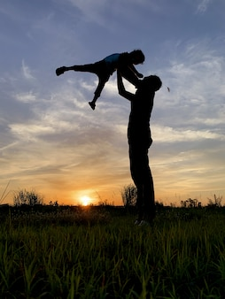 Profili il padre carrying son against sky durante il tramonto