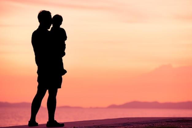 Profili il padre ed il figlio sulla spiaggia nel tempo del tramonto con il cielo crepuscolare