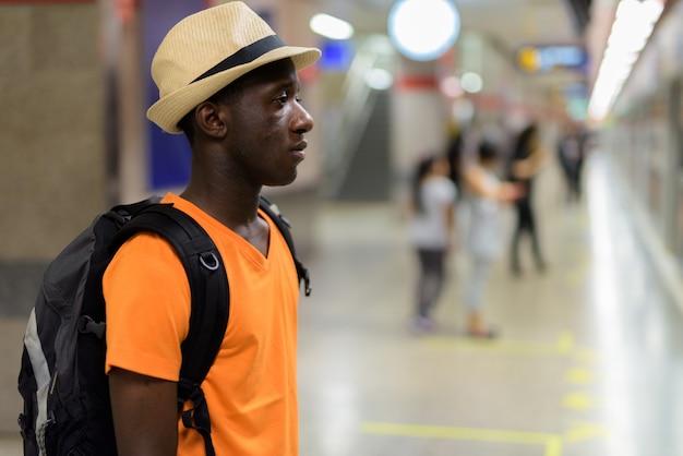 Profili il punto di vista del treno aspettante del giovane uomo turistico nel sottopassaggio di bangkok tailandia