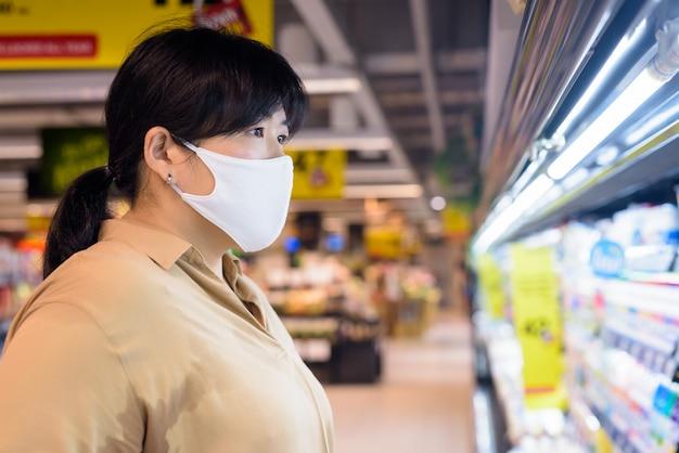 Profili il punto di vista della donna asiatica di peso eccessivo con acquisto della maschera dentro il supermercato