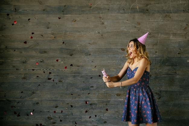Profili il punto di vista di bella donna allegra che fa scoppiare i coriandoli, celebrando una festa