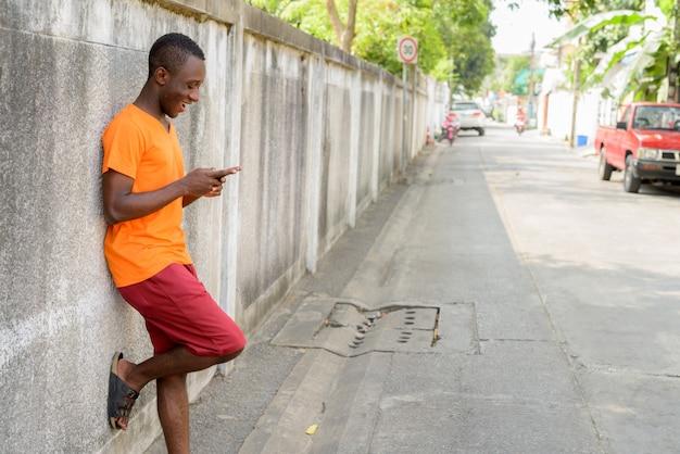 Profili il punto di vista di giovane uomo felice che sorride mentre per mezzo del telefono cellulare e appoggiandosi contro la vecchia parete del cemento nelle vie all'aperto