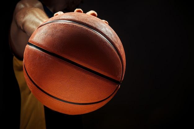Profili il punto di vista di una palla del canestro della tenuta del giocatore di pallacanestro su fondo nero