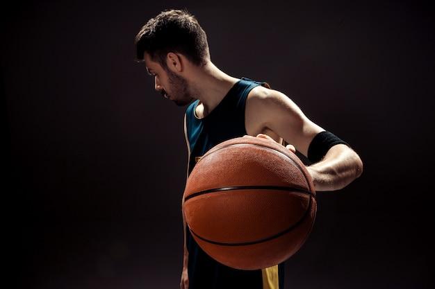 Profili il punto di vista di una palla del canestro della tenuta del giocatore di pallacanestro sul nero